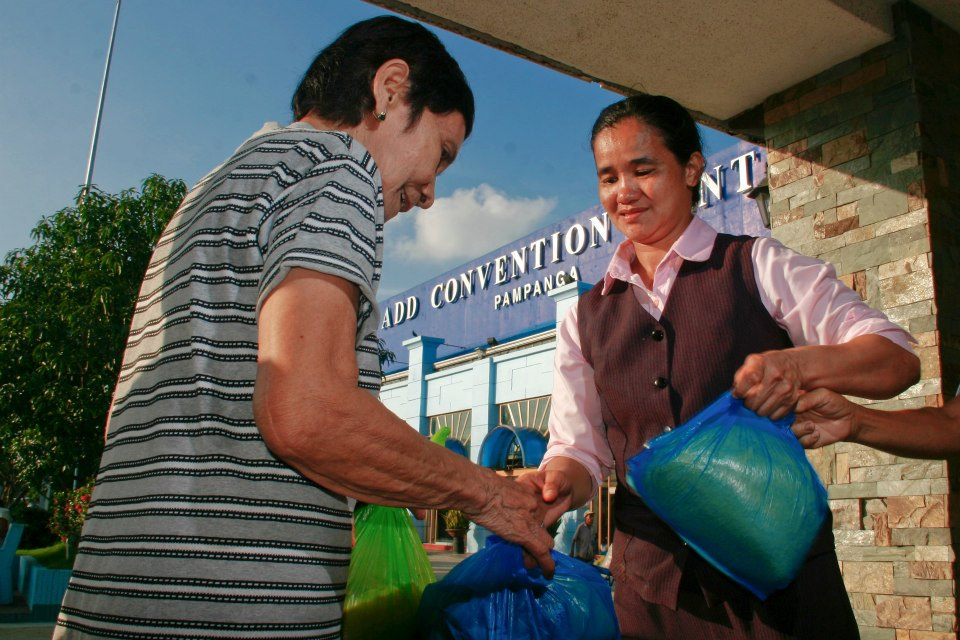 A Church member gives relief goods to a resident of Apalit, Pampanga when floods due to continuous rain hit the town in 2012.