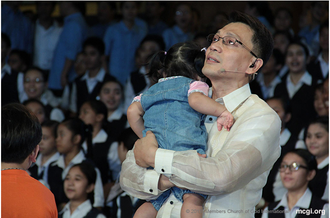 Looking at the big LED screen on stage, Bro. Daniel Razon carries his daughter as the whole congregation offers a song of praise to God.