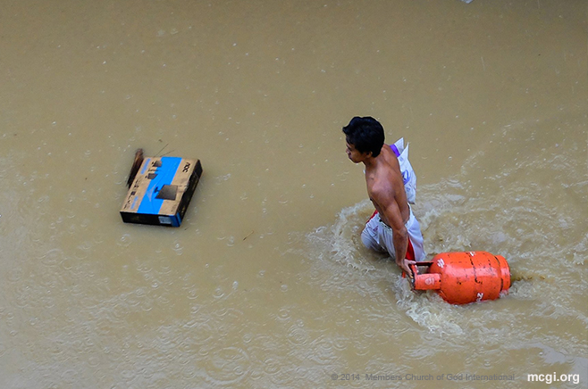 A man pulls a gas tank on a flooded street in Marikina, Philippines during the siege of Typhoon Fung Wong (Mario) on September 19, 2014. (Photo courtesy of Photoville Intenational)