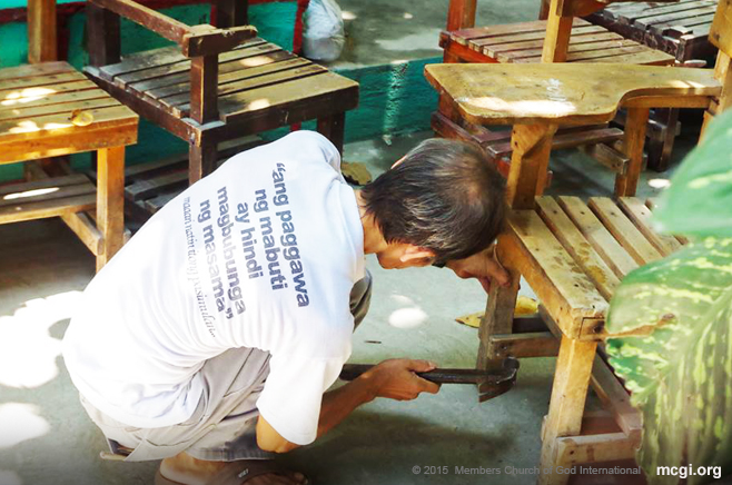 An elderly brother repairing a worn-down classroom chair during a Brigada Eskwela project held in Maria Concepcion Cruz High School in Pateros, Manila. (Photo courtesy of Photoville International)