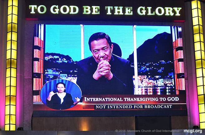An interpreter for the deaf and mute does sign language as Bro. Eli Soriano speaks to MCGI brethren around the world via satellite and the internet. (Photo courtesy of Photoville International)