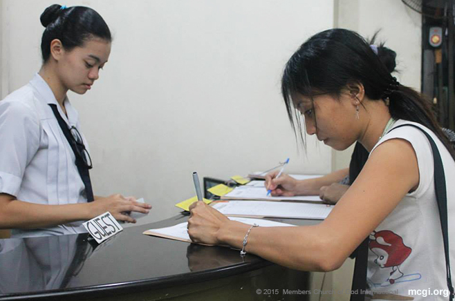 A female guest logging her name at the attendance table in the Muñoz Coordinating Center. (Photo courtesy of Photoville International)