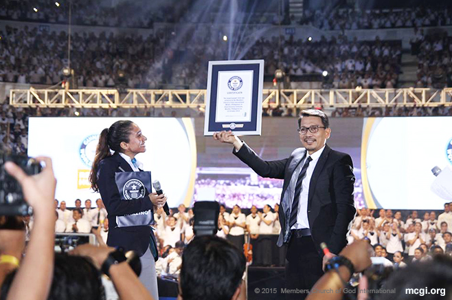 Bro. Daniel Razon proudly holds up the Guinness World Records plaque for Ang Dating Daan Chorale's musical feat of being the Largest Gospel Choir in the world, presented by Guinness Adjudicator Ms. Fortuna Burke Melhelm. (Photoville International)