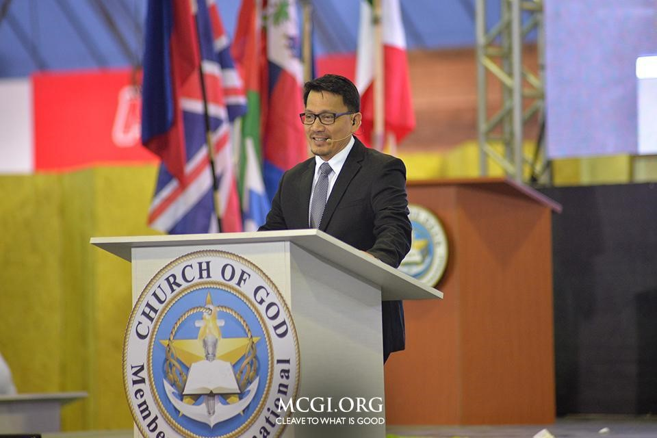 Bro. Daniel Razon, Assistant Overall Servant, smiles as he delivers a biblical topic in Filipino, with a live translation in Portuguese and Spanish. (Photo courtesy of Photoville International)