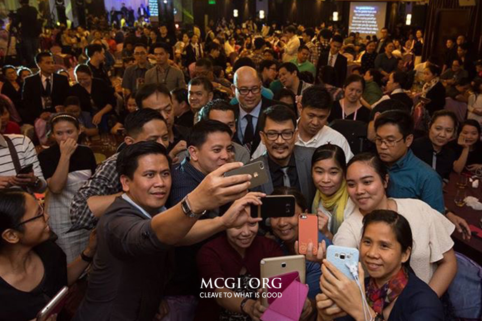 "Bro. Daniel Razon, Assistant Overall Servant to MCGI, is surrounded by brethren and take photos with them during the ""Labour of Love"" Benefit Concert held in Hong Kong on May 1, 2016. (Photo courtesy of MCGI-Photoville/ Jeffrey Navarro)"